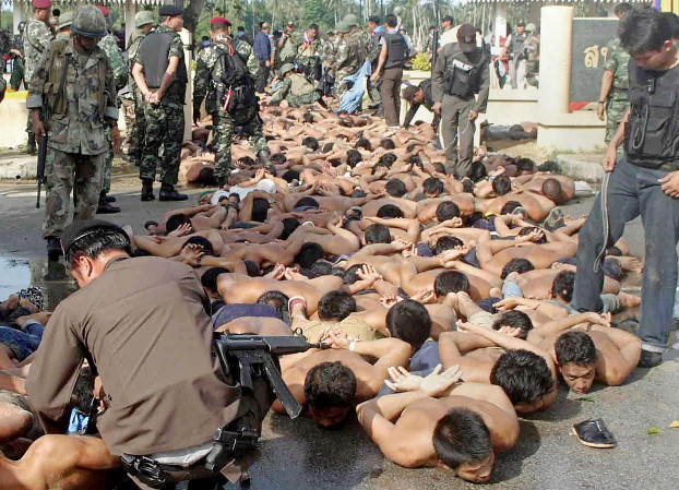 Demonstrators lie on the pavement after their arrest oustide Tak Bai police station in Narathiwat province, Thailand, Oct. 25, 2004.