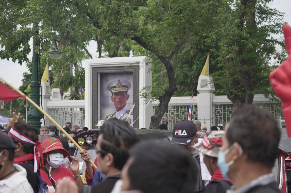 Anti-government protesters walk past a portrait of King Maha Vajiralongkorn in a Bangkok street, Sept. 19, 2020. [Nontarat Phaicharoen/BenarNews]