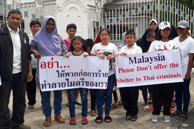 """Members of an activist group, """"Deep South Peaceful Thais,"""" hold signs outside the Malaysian Consular office in southern Thailand's Songkhla province, urging Malaysia to stop supporting insurgents, Oct. 24, 2018. (Mariyam Ahmad/BenarNews)"""