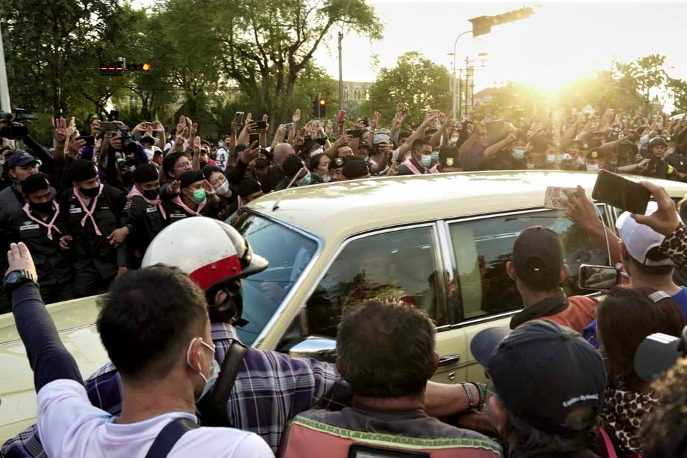 Pro-democracy protesters surround a car carrying Queen Suthida and her stepson, Prince Dipangkorn Rasmijoti, near Government House in Bangkok, Oct. 14, 2020. [Courtesy of Thiti Pleetong]