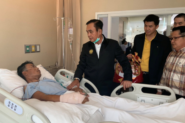 Prime Minister Prayuth Chan-o-cha visits an injured man in a hospital following a gun battle involving a Thai soldier on a shooting rampage, in Korat, Thailand, Feb. 9, 2020. [Government House/Handout via Reuters]