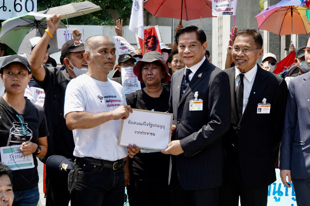 Anusorn Unno of Thammasat University submits the protesters' demands to Pirapan Salirathavibhaga, an adviser to Prime Minister Prayuth Chan-o-cha, in front of parliament, March 13, 2020. [Nontarat Phaicharoen/BenarNews]