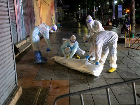 Health workers prepare to take away the body of a person who died on the street, possibly of COVID-19, in Bangkok, July 20, 2021.