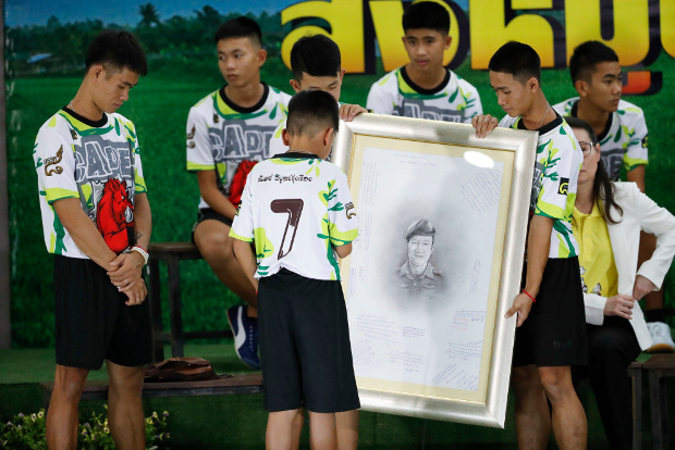 Coach Ekkapol Janthawong (left) and members of the Wild Boars team pay respect as they hold a portrait of Saman Kunan, the retired Thai SEAL who died in the Tham Luang cave prior to their rescue, during a press conference in Chiang Rai, northern Thailand, July 18, 2018. (AP)
