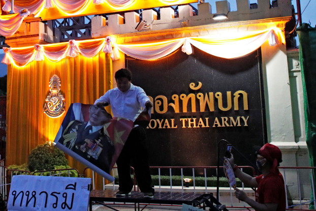 An anti-government activist tears a portrait of army chief Gen. Apirat Kongsompong during a protest in front of Royal Thai Army headquarters in Bangkok, July 20, 2020. [Reuters]