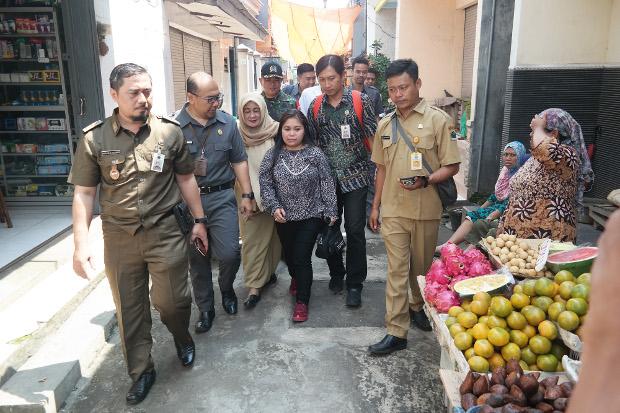 Dyah Anggraeni (tengah) didampingi petugas Kementerian Tenaga Kerja dan P4TKI berjalan menuju rumahnya di Kelurahan Kebalen, Kedungkandang, Kota Malang, Jawa Timur, 19 Februari 2019. (Eko Widianto/BeritaBenar)