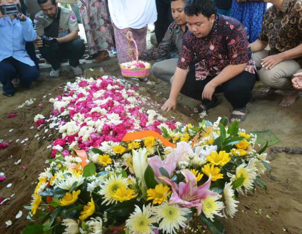 Putra sulung Sutopo, Muhammad Ivanka Rizaldy Nugroho berdoa di pusara ayahnya usai dimakamkan di TPU Sonolayu Boyolali, Jawa Tengah, 8 Juli 2019. (Kusumasari Ayuningtyas/BeritaBenar)