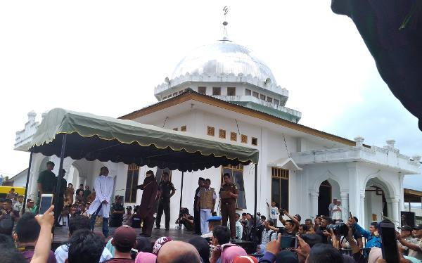 Warga mengabadikan prosesi eksekusi cambuk di halaman Masjid Babussalam di Banda Aceh, 27 Februari 2018. (Nurdin Hasan/BeritaBenar)