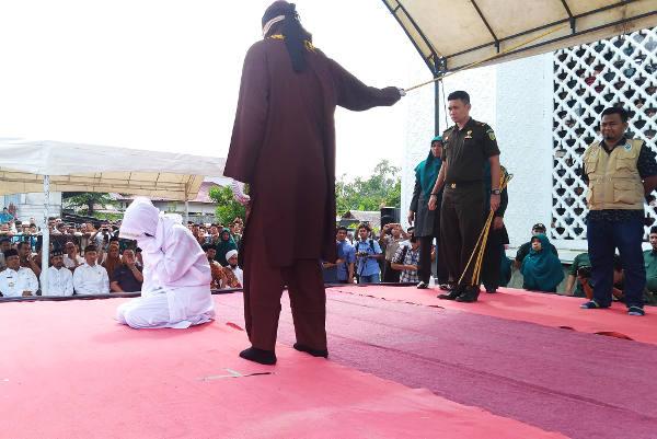 Novia Sri Wahyuni menutup wajahnya ketika dicambuk algojo di Banda Aceh, 19 Januari 2018. (Nurdin Hasan/BeritaBenar)