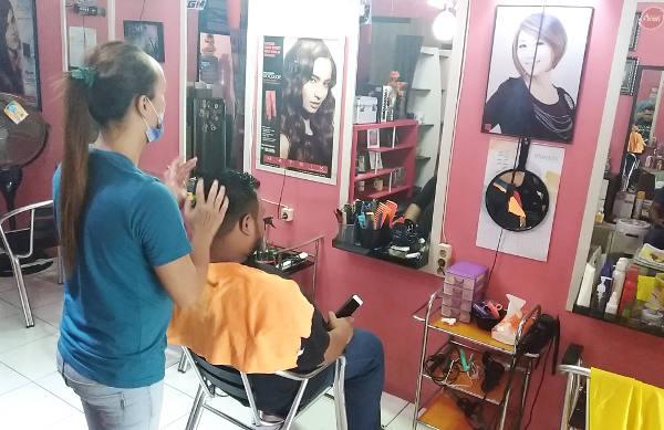 Seorang waria memijat kepala pelanggannya setelah dipangkas rambut di Banda Aceh, 3 Februari 2018. (Nurdin Hasan/BeritaBenar)