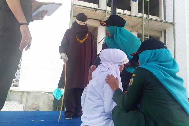 Petugas Wilayatul Hisbah berusaha menenangkan seorang perempuan yang menangis kesakitan saat dicambuk di Banda Aceh, 1 Agustus 2019. (Nurdin Hasan/BeritaBenar)