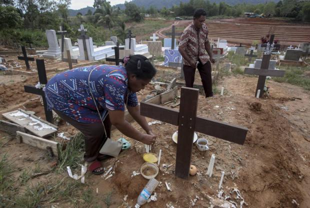 Seorang pekerja migran Indonesia meletakkan lilin di atas makam suaminya yang bekerja di perkebunan kelapa sawit di Sabah, Malaysia, 9 Desember 2018. Jenazah buruh migran yang meninggal terkadang tidak dikirim kembali ke Indonesia. (AP)