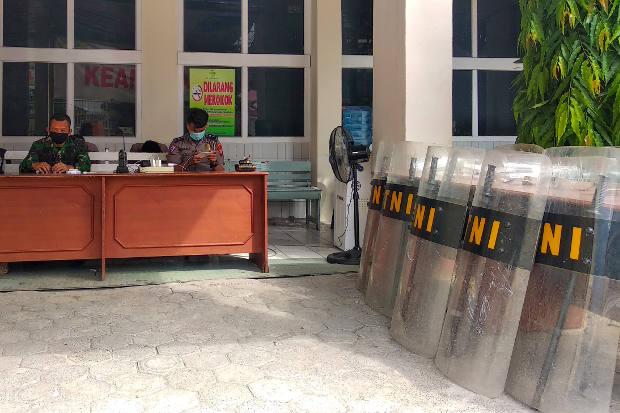 Polisi dan tentara duduk bersiaga sementara alat pelindung anti huru-hara tampak berjajar di dekat mereka di RS Stella Maris di Makassar, Sulawesi Selatan, 12 Juni 2020. Sebelumnya sejumlah anggota keluarga dari jenazah pasien COVID-19 berusaha mengambil jenazah dari sejumlah rumah sakit untuk dimakamkan oleh mereka sendiri tanpa mengikuti prosedur keamanan penanggulangan COVID-19. [AFP]