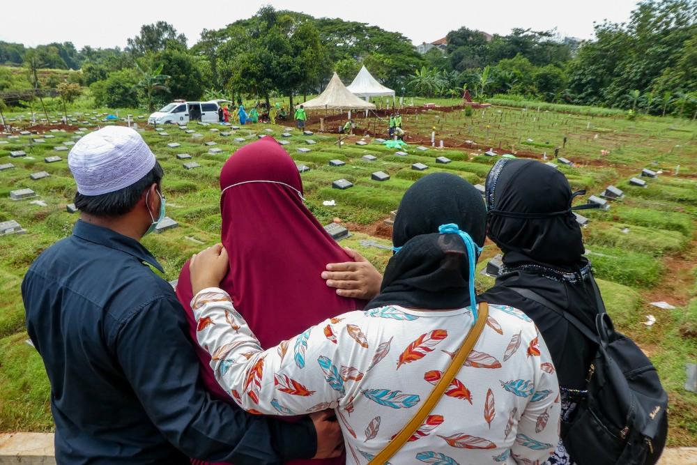 Sanak keluarga meratapi kepergian salah seorang anggota keluarga mereka yang meninggal karena virus corona, di sebuah pemakaman di Jakarta, 31 Maret 2020. [AFP]