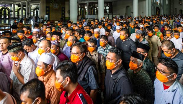 Di tengah wabah COVID-19, jemaah menggunakan masker melakukan salat Jumat di sebuah masjid di Surabaya, 20 Maret 2020. [AFP]