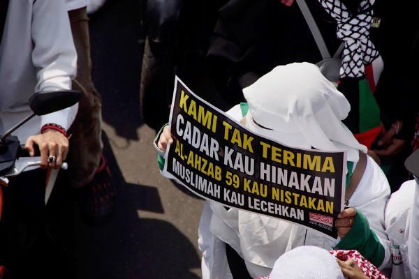 Seorang perempuan membawa poster saat aksi unjuk rasa di Jakarta, 6 April 2018. (Arie Firdaus/BeritaBenar)