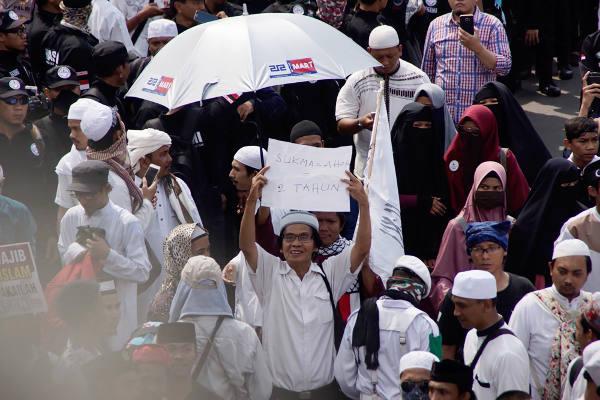 Seorang warga mengangkat poster ketika ikut aksi unjuk rasa di depan Bareskrim Polri, Jakarta, 6 April 2018. (Arie Firdaus/BeritaBenar)