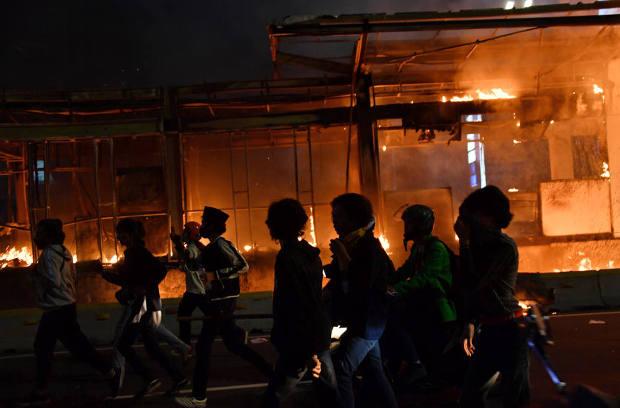 Para pengunjuk rasa melarikan diri dari semprotan gas air mata polisi dengan latar belakang bangunan yang dibakar dalam demonstrasi buruh dan mahasiswa menentang pengesahan Undang-Undang Cipta Kerja yang dinilai mengorbankan hak-hak buruh dan lingkungan hidup, di Jakarta, 8 Oktober 2020. [AFP]