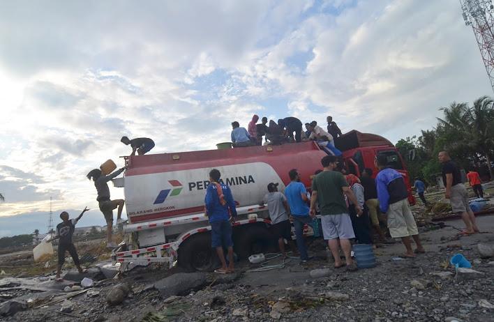 Sejumlah warga menjarah mobil pengangkut bahan bakar minyak yang melintas di Kota Palu, 1 Oktober 2018. (Yayank Stiv/BeritaBenar)