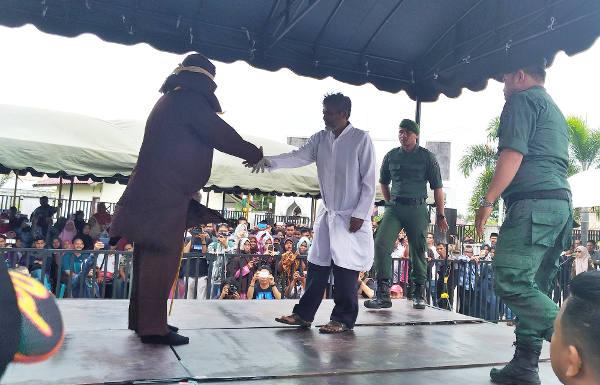 Ridwan MR bersalaman dengan algojo usai dicambuk 19 kali di Banda Aceh, 27 Februari 2018. (Nurdin Hasan/BeritaBenar)
