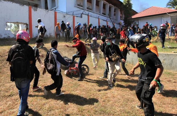 Para mahasiswa merusak sebuah sepeda motor di lokasi gedung DPRD Sulawesi Tenggara di  tengah-tengah protes menolak UU KPK, RUU KUHP, dan peraturan lainnya yang dianggap tidak pro rakyat, di Kendari, Sulawesi Tenggara, 26 September 2019. (Reuters)