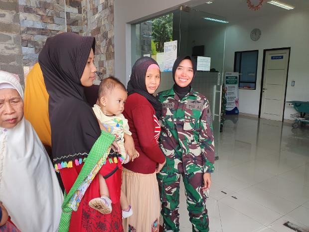 Tansya Susan, anggota pasukan perdamaian Indonesia, berpose bersama warga yang turut serta mendapatkan pelayanan kesehatan gratis di klinik Pusat Misi Pemeliharaan Perdamaian (PMPP) TNI di Sentul, Jawa Barat, 6 Agustus 2019. (Ahmad Syamsudin/BeritaBenar)