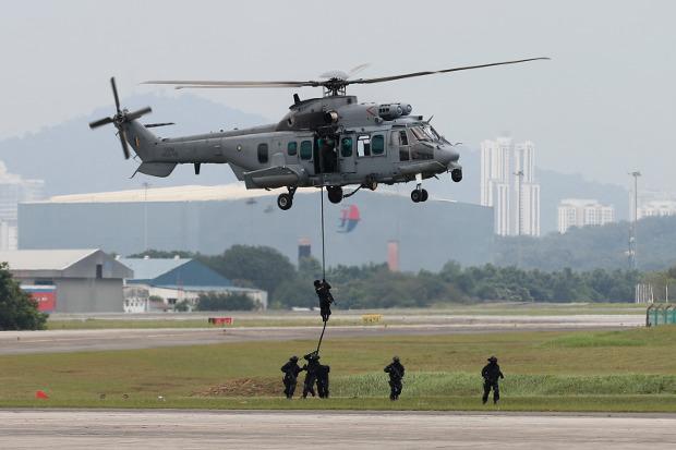 Pasukan khusus mendemonstrasikan keahlian mereka dalam latihan penanganan terorisme dari helikopter sesudah peluncuran patroli gabungan antara Malaysia, Indonesia dan Filipina di pangkalan militer Subang, di Petaling Jaya, Malaysia, 12 Oktober 2017. [AP]