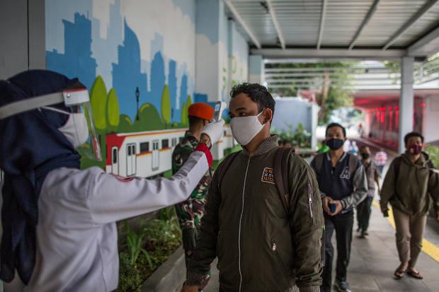 Petugas Stasiun Kereta Komuter memeriksa suhu tubuh calon penumpang di Stasiun Sudirman, Jakarta, 5 Juni 2020. [Afriadi Hikmal/BenarNews]
