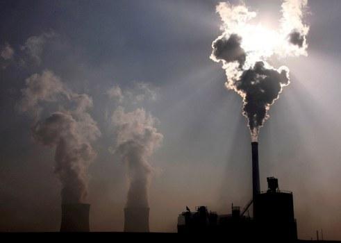 Pembangkit listrik tenaga batu bara terlihat di belakang sebuah pabrik di Baotou, di Kawasan Otonomi Mongolia Dalam di Cina. [Reuters]