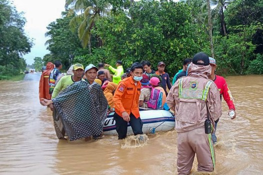 Foto yang diambil dan dirilis pada 15 Januari 2021 oleh Badan Nasional Penanggulangan Bencana Indonesia (BNPB) ini menunjukkan para penyelamat mengevakuasi penduduk desa dengan perahu karet di daerah banjir di kabupaten Tanah Laut, Kalimantan Selatan.[AFP]