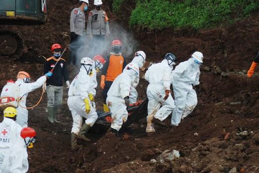 Tim penyelamat didesinfeksi saat mereka mengeluarkan tubuh korban longsor yang menewaskan total 40 orang di Sumedang, Jawa Barat, pada 17 Januari 2021. [AFP]