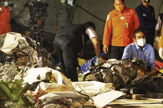 Petugas memeriksa potongan-potongan puing pesawat yang ditemukan dari lokasi jatuhnya penerbangan Sriwijaya Air SJY182, di Pelabuhan Tanjung Priok, Jakarta, 15 Januari 2021. [AFP]