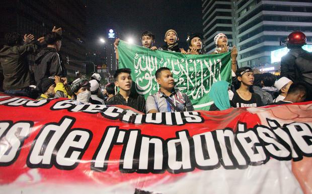 Pengunjuk rasa yang membawa spanduk dalam berbagai bahasa, bertahan meski sudah malam di depan kantor Bawaslu, Jakarta, 22 Mei 2019. (Keisyah Aprilia/BeritaBenar)