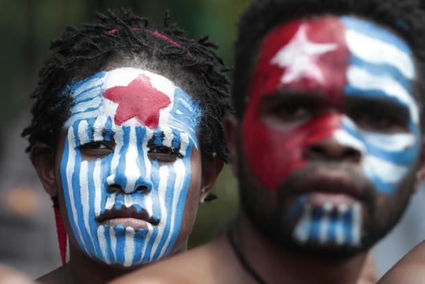 Aktivis Papua mewarnai muka mereka dengan warna lambang Bintang Kejora, simbol gerakan separatis Organisasi Papua Merdeka, saat berdemonstrasi di dekat Istana Negara di Jakarta, 22 Agustus 2019. (AP)