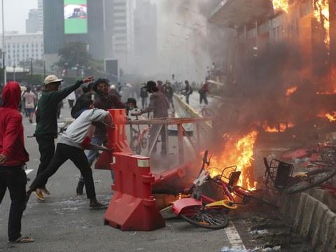 Para pengunjuk rasa membakar sebuah stasiun MRT di Jakarta, dalam protes massal menentang Undang-Undang Cipta Kerja yang diinisiasi pemerintah untuk menggenjot investasi tapi disinyalir melumpuhkan hak-hak buruh dan merusak lingkungan, Kamis, 8 Oktober 2020.
