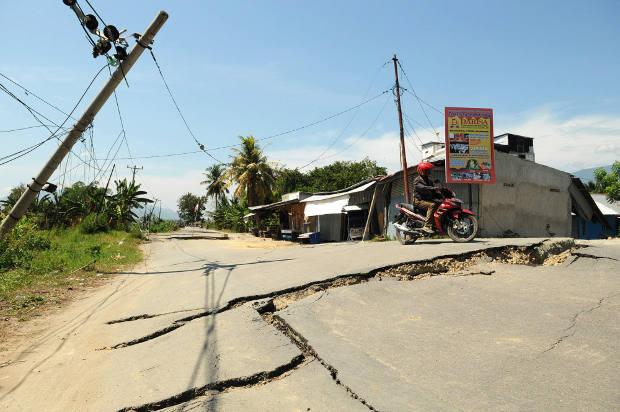 Seorang pengendara sepeda motor berusaha menghindar dari jalan yang hancur akibat gempa di Kabupaten Sigi, Sulawesi Tengah, 7 Oktober 2018. (Keisyah Aprilia/BeritaBenar)