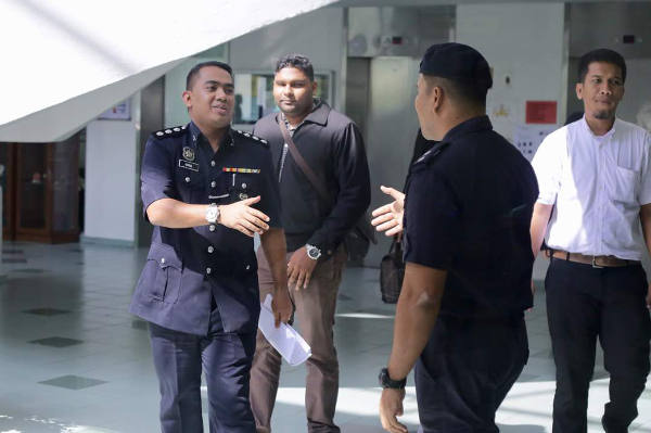 Wan Azirul Nizam Che Wan Aziz (kiri), penyidik kasus pembunuhan Kim Jong-nam, meninggalkan Pengadilan Tinggi di Shah Alam setelah bersaksi dalam persidangan terhadap dua perempuan yang didakwa membunuh Kim Jong-nam, 25 Oktober 2017.