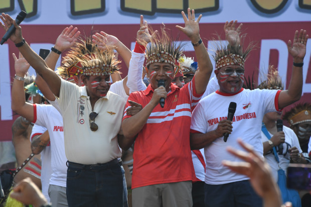 Menko Polhukam Wiranto (tengah) bernyanyi bersama ratusan warga Papua dan warga Jakarta di ibu kota dalam acara musik dan tarian Yospan Papua di Bundaran Hotel Indonesia (HI), Jakarta, Minggu, 1 September 2019. (AFP)