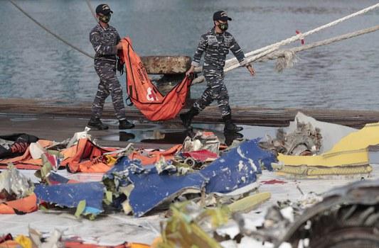 Tentara Angkatan Laut membawa kantong jenazah yang berisi potongan tubuh korban jatuhnya pesawat Sriwijaya Air SJ-di Pelabuhan Tanjung Priok, Jakarta, 21 Januari 2021. [AP]
