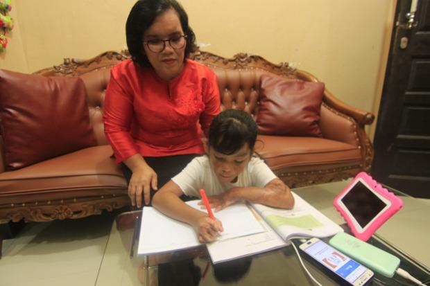 """Sarina Gultom menemani putrinya, Trinity Hutahean (7), mengerjakan tugas sekolahnya, di rumahnya di Samarinda, Minggu (11/10/2020).""""Saya minta Trinity menutupi kekurangan fisik dengan kemampuan akademis,"""" ujar sang Ibu. [BenarNews]"""