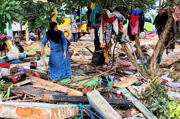 Seorang warga mengumpulkan pakaian yang masih bisa digunakan di Kecamatan Sumur, Kabupaten Pandeglang, Banten, 26 Desember 2018. (Keisyah Aprilia/Berita Benar)