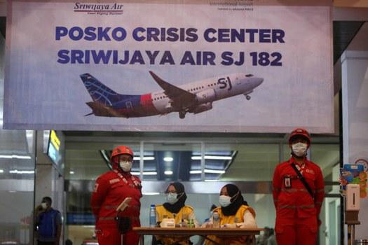 Sejumlah petugas berdiri di depan posko crisis center Sriwijaya Air SJ-182 di Bandara International Soekarno Hatta, Tanggerang, Banten, pada hari pesawat tersebut jatuh di sekitar perairan Kepulauan Seribu di Laut Jawa, 9 Januari 2021. [Araminta JR/BenarNews]