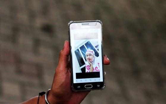 Seorang warga memperlihatkan layar telepon genggamnya yang berisi foto anggota keluarganya yang merupakan penumpang pesawat Sriwijaya Air SJ-182, di pos ante mortem RS Polri Kramat Jati di Jakarta, 12 Januari 2021. [Anhar Rizki Affandi/BenarNews]
