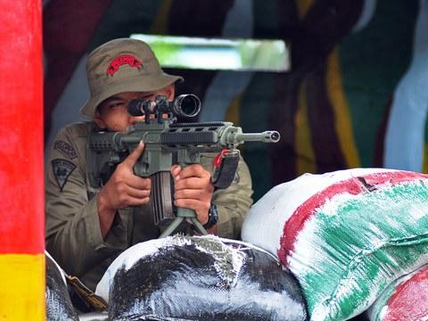 Seorang petugas Brimob melakukan penjagaan di markas kepolisia di Poso, Sulawesi Tengah, sehari setelah tersangka militan menembak mati tiga polisi di daerah tersebut, 21 Desember 2012.