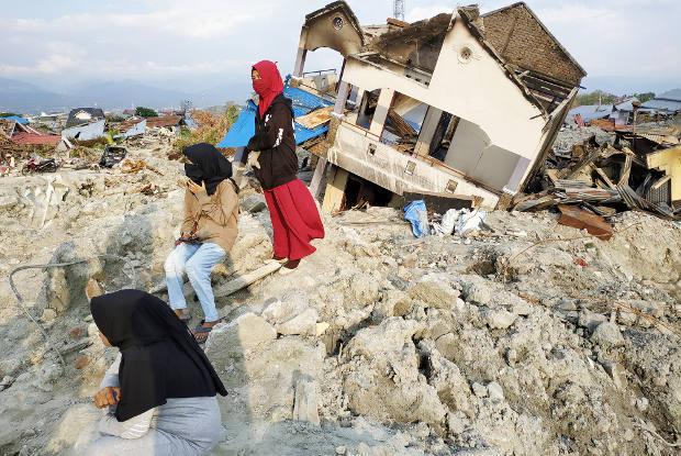 Tiga orang warga terlihat di kelurahan Balaroa, Palu, Sulawesi Tengah, yang hancur akibat gempa dan likuefaksi, 17 Oktober 2018. (Keisyah Aprilia/BeritaBenar)