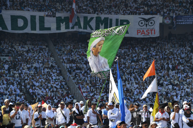 Para pendukung Prabowo Subianto memegang bendera bergambar pemimpin kelompok Islam garis keras, Front Pembela Islam (FPI), Rizieq Shihab, dalam kampanye calon presiden itu di Stadion Gelora Bung Karno di Jakarta, 7 April 2019. (AFP)