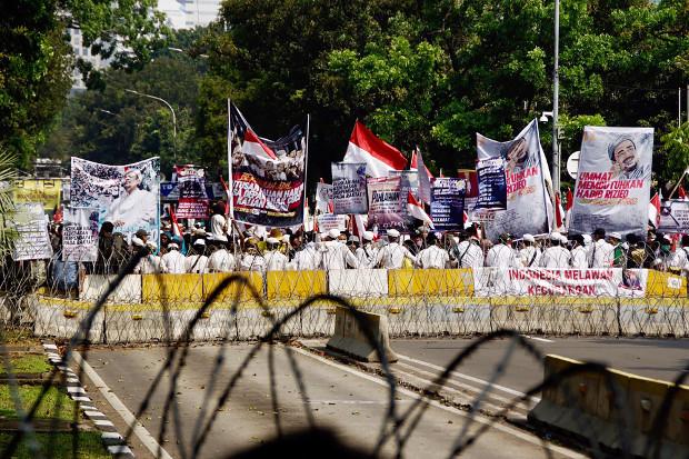 Para pengunjuk rasa membawa poster dan bendera ketika menggelar aksi dekat gedung Mahkamah Konstitusi di Jakarta, saat sidang putusan gugatan Pilpres, 27 Juni 2019. (Arie Firdaus/BeritaBenar)