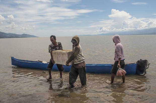 Dua warga mengangkat kotak gabus berisi udang kecil dari perahu di pantai Kelurahan Lere, Kota Palu, Sulawesi Tengah, 23 Juni 2019. (Keisyah Aprilia/BeritaBenar)