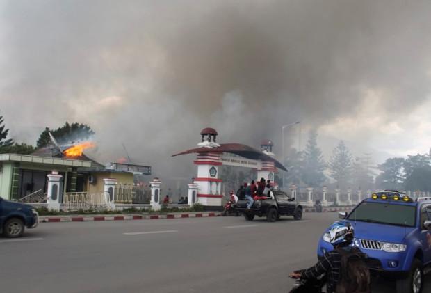 Warga berkendara melewati gedung pemerintah yang terbakar saat protes yang berubah menjadi kerusuhan di Wamena, Provinsi Papua, 23 September 2019. (AP)