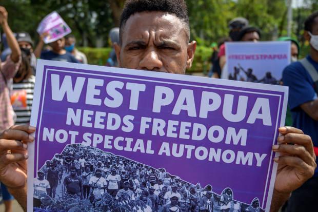 Membawa poster, mahasiswa Papua melakukan unjuk rasa di Jakarta, 15 Agustus 2020. (AFP)